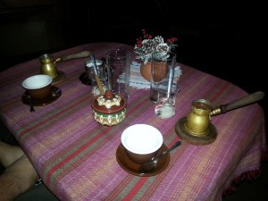 Coffee service with djzhezve, cups, and spoonfulls of byalo sladko in water